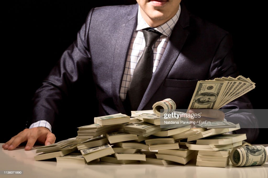 Midsection Of Businessman With Paper Currency Against Black Background : Stock Photo
