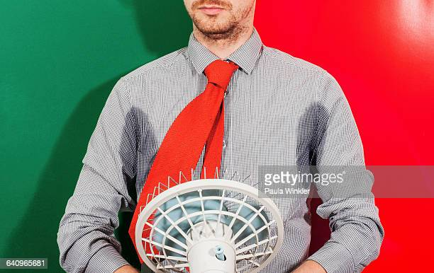 Midsection of businessman with sweaty armpits holding fan against colored background