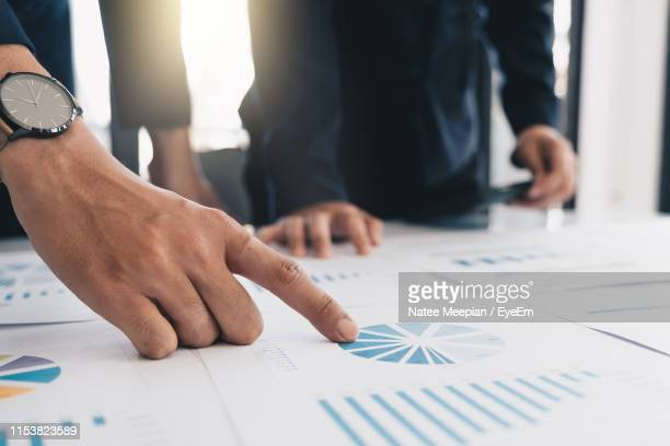 midsection of businessmen analyzing charts on desk in office - report document ストックフォトと画像