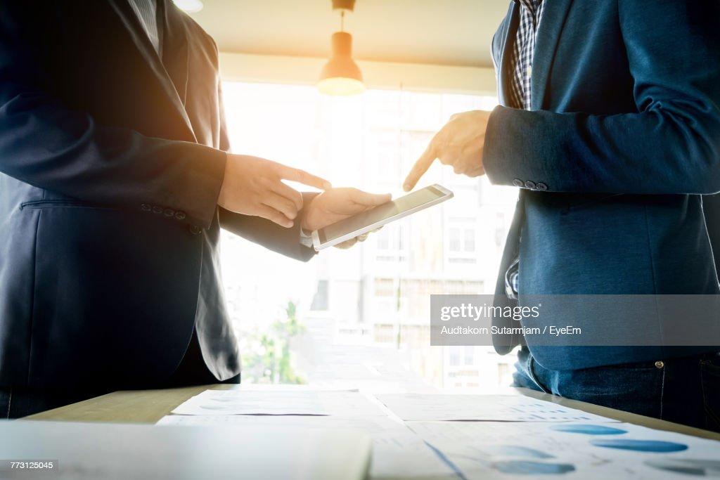 Midsection Of Businessmen Using Digital Tablet : Stock Photo