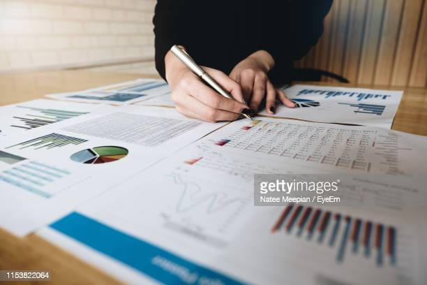 midsection of businesswoman analyzing reports on desk in office - report document ストックフォトと画像