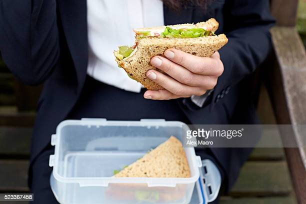 Mid-section of businesswoman eating lunch