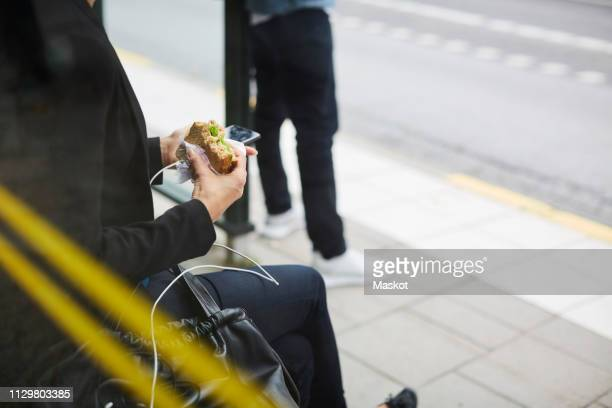 midsection of businesswoman eating sandwich while sitting with smart phone at bus stop in city - mensch im hintergrund stock-fotos und bilder