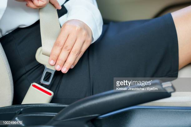 midsection of businesswoman fastening seat belt in car - fastening stock pictures, royalty-free photos & images