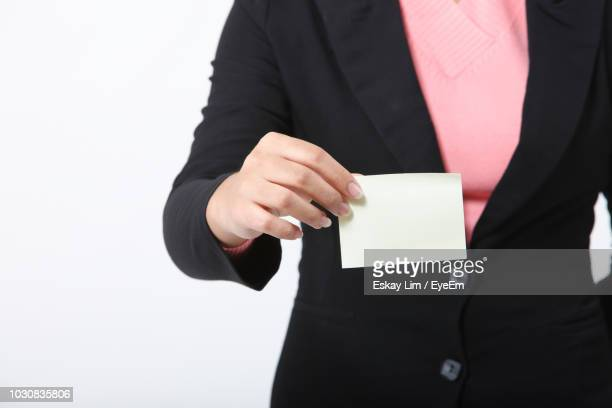 Midsection Of Businesswoman Holding Blank Card Over White Background