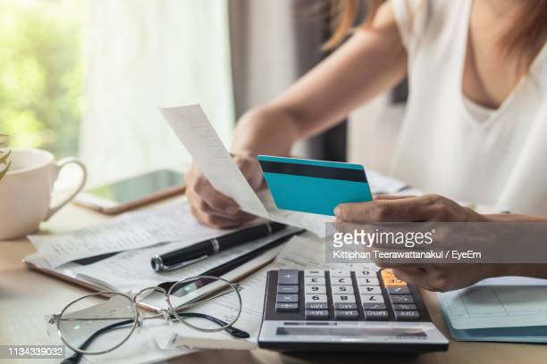 midsection of businesswoman holding credit card and bill while working at desk - financial bill stock pictures, royalty-free photos & images