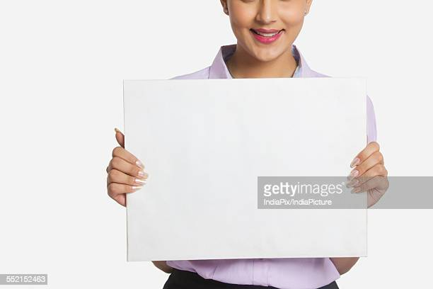 Midsection of businesswoman holding empty placard over white background