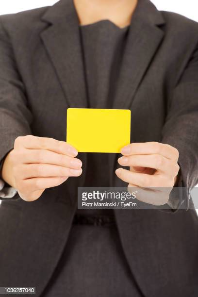 Midsection Of Businesswoman Holding Yellow Card Against White Background