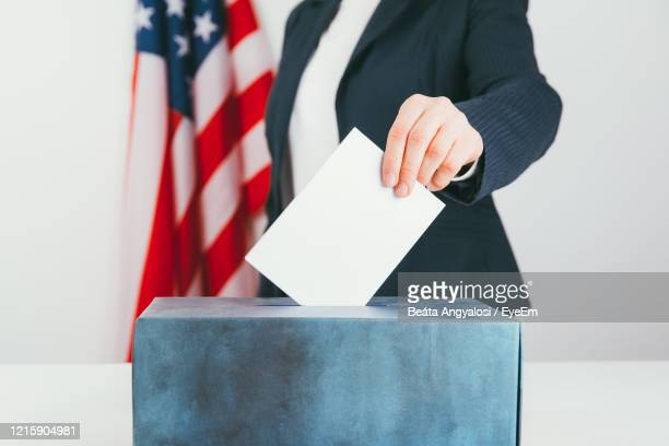 midsection of businesswoman inserting letter in ballot box on table - election stock pictures, royalty-free photos & images