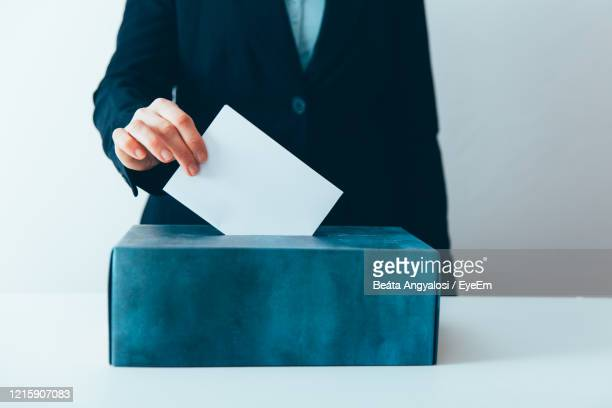 midsection of businesswoman inserting letter in ballot box on table - ballot box stock pictures, royalty-free photos & images