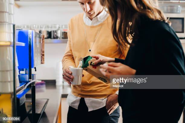 midsection of businesswoman pouring milk in glass from carton for businessman at office cafeteria - milk carton fotografías e imágenes de stock