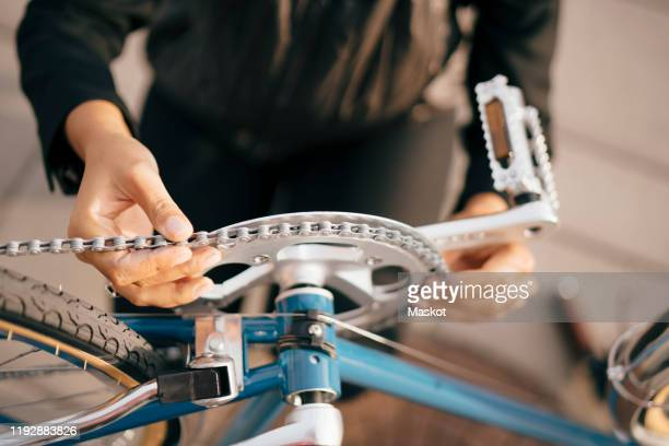 midsection of businesswoman repairing bicycle in city - repairing stock pictures, royalty-free photos & images