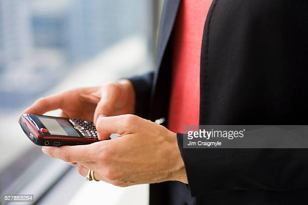 Midsection of businesswoman text-messaging