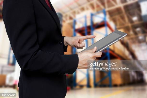 Midsection Of Businesswoman Using Digital Tablet While Standing In Warehouse