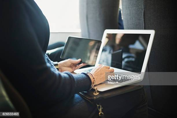 Midsection of businesswoman using laptop and digital tablet in train
