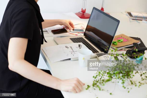 Midsection of businesswoman using mobile phone with laptop and document on table in office