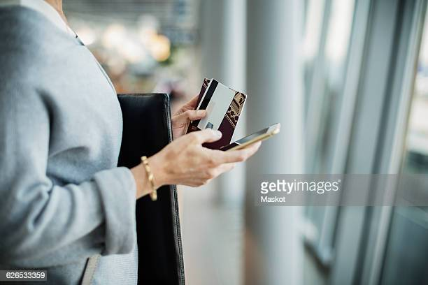 Midsection of businesswoman using smart phone at airport