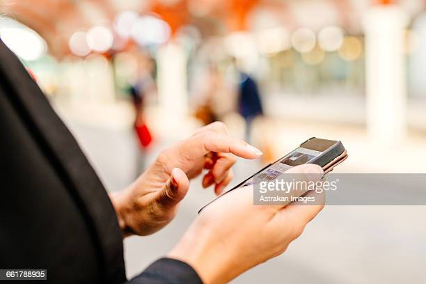 Midsection of businesswoman using smart phone at railroad station