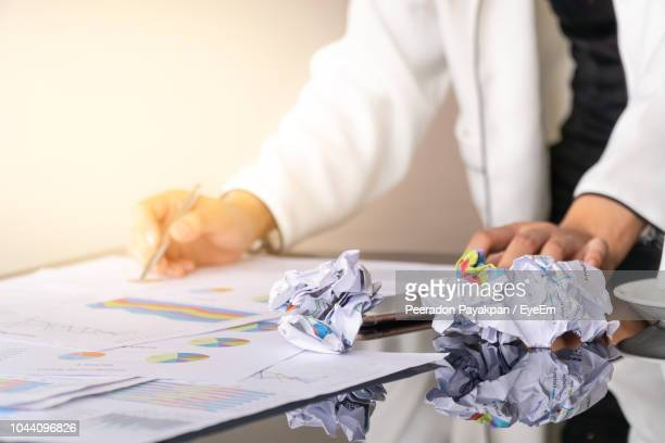 Midsection Of Businesswoman With Crumpled Documents Working In Office