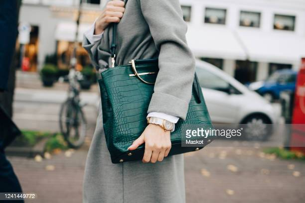 midsection of businesswoman with handbag standing in city - evening bag stock pictures, royalty-free photos & images