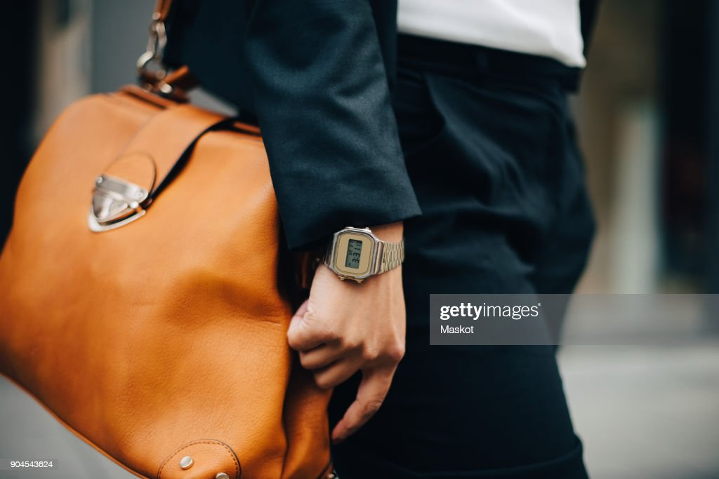 Midsection of businesswoman with orange purse standing in city : Stock Photo