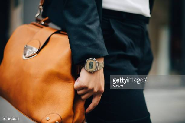 midsection of businesswoman with orange purse standing in city - clutch bag stock pictures, royalty-free photos & images