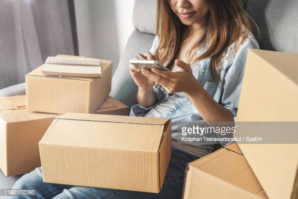 midsection of businesswoman with packages using smart phone while sitting at home - viele gegenstände stock-fotos und bilder