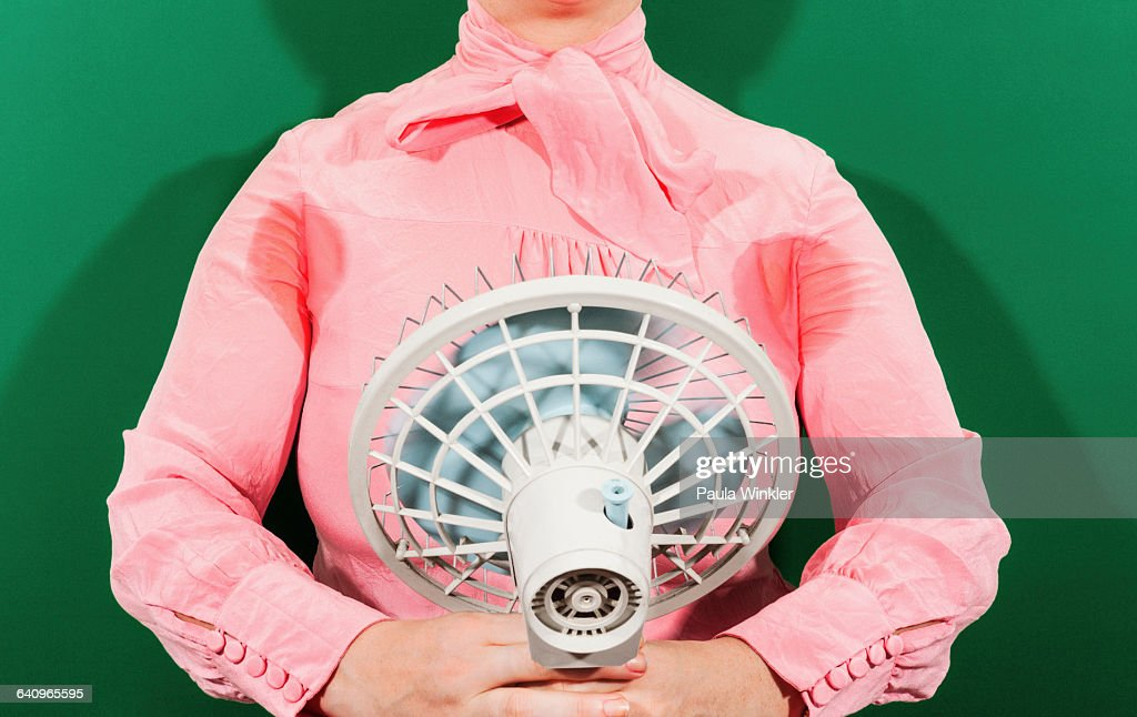Midsection of businesswoman with sweaty armpits holding fan against green background : Stock Photo