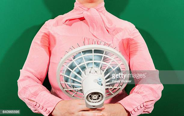 Midsection of businesswoman with sweaty armpits holding fan against green background