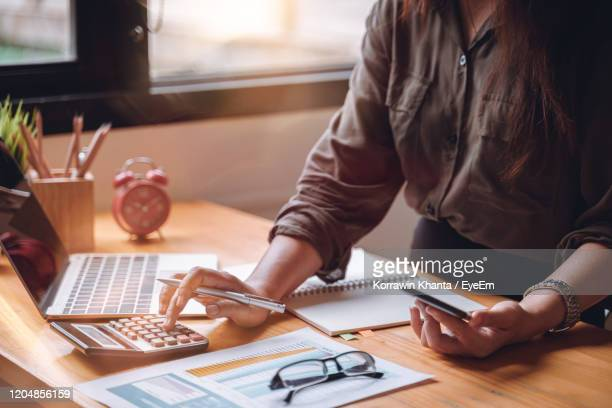 midsection of businesswoman working at table in office - people stock pictures, royalty-free photos & images
