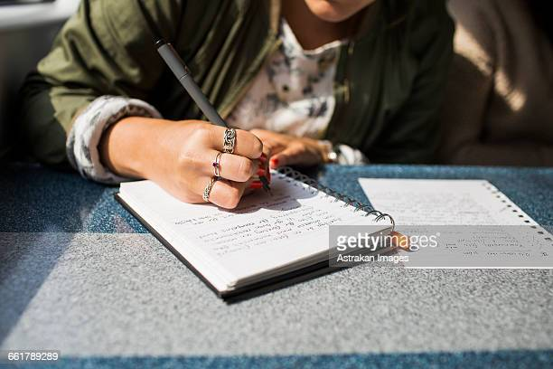 midsection of businesswoman writing on diary in train - diary stock pictures, royalty-free photos & images