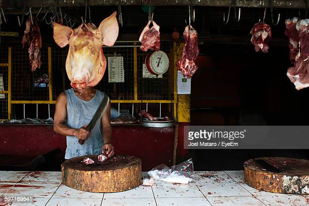 Midsection Of Butcher Cutting Meat At Butcher Shop