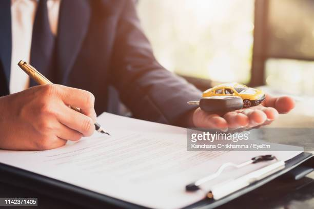 midsection of car insurance agent writing on form while holding key at office - car insurance stock pictures, royalty-free photos & images