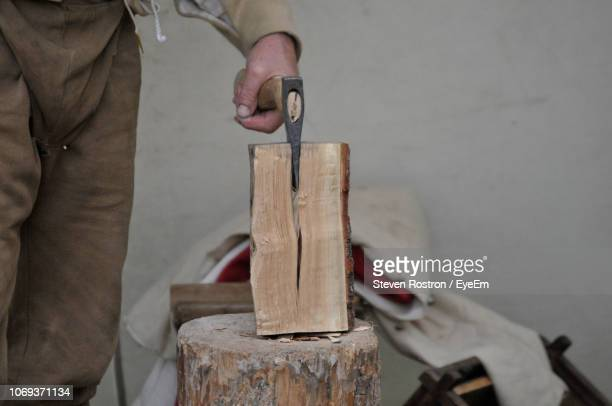 midsection of carpenter cutting wood on tree stump - chopped stock pictures, royalty-free photos & images