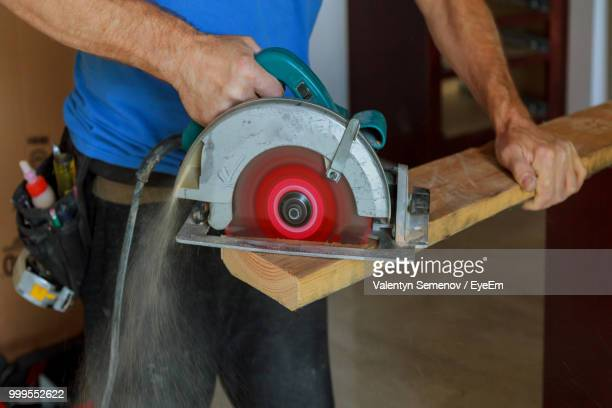 midsection of carpenter cutting wood - circular saw stock photos and pictures