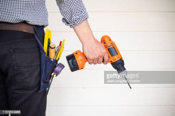 midsection of carpenter holding drill against wall - drill stock pictures, royalty-free photos & images