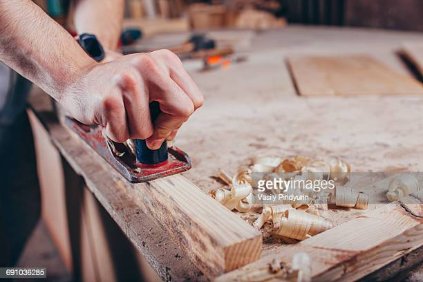 Midsection of carpenter planing wood at workshop