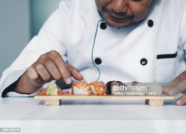 Midsection Of Chef Arranging Sushi On Cutting Board