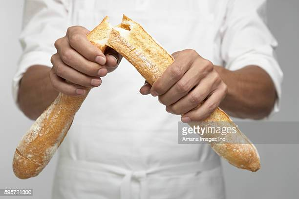 Midsection of Chef Breaking Baguette