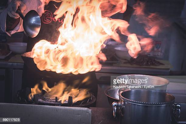 Midsection Of Chef Cooking Food In Flames