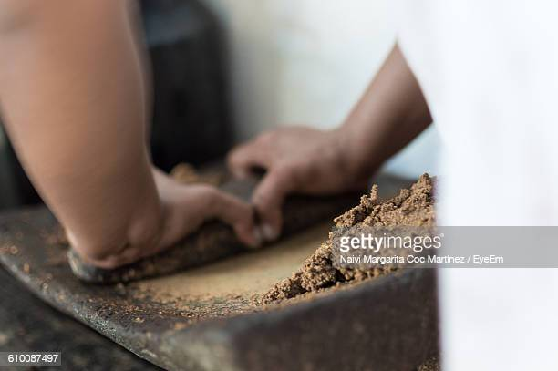 Midsection Of Chef Crushing Cocoa On Mortar