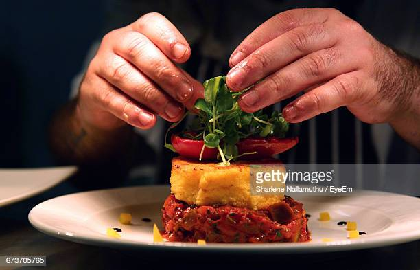 Midsection Of Chef Garnishing Food At Table