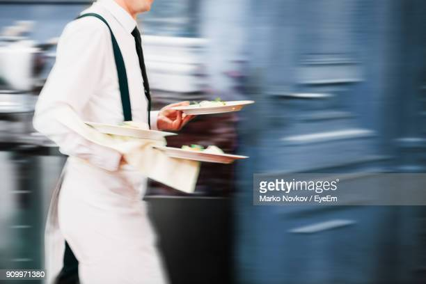 midsection of chef holding food while walking in restaurant - wait staff stock pictures, royalty-free photos & images