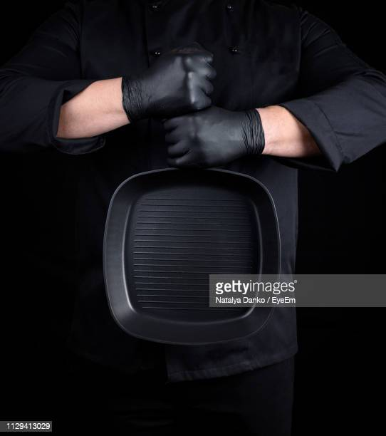 midsection of chef holding frying pan against black background - black glove stock pictures, royalty-free photos & images