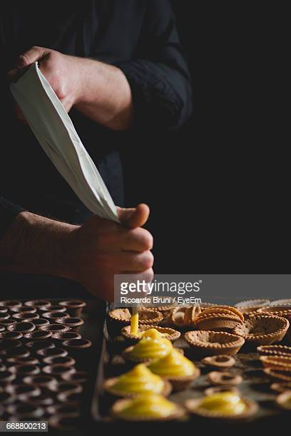 Midsection Of Chef Making Pastries With Piping Bag In Bakery