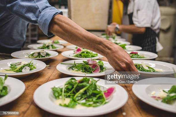 Midsection Of Chef Making Salad In Kitchen