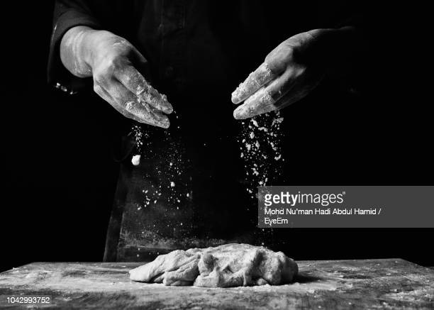 midsection of chef preparing food against black background - black and white food stock pictures, royalty-free photos & images