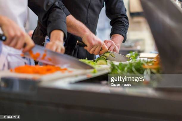midsection of chefs chopping vegetables at restaurant kitchen - chopping food stock pictures, royalty-free photos & images