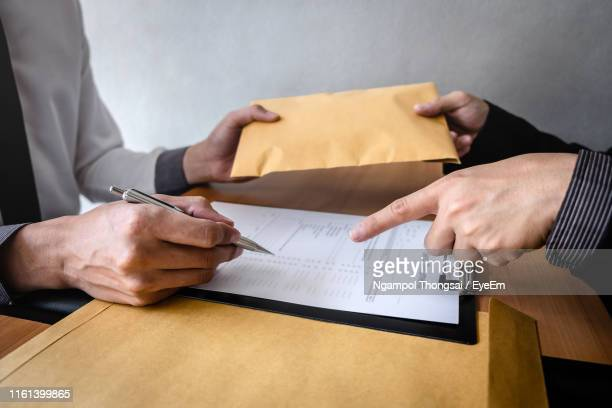 midsection of colleagues at office - corruption stock pictures, royalty-free photos & images