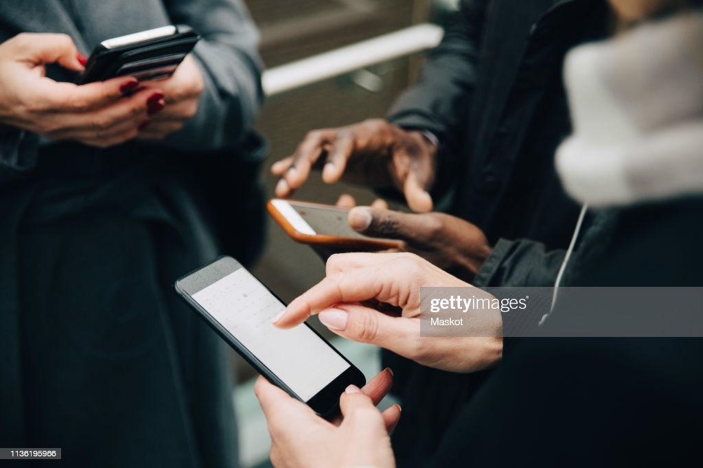 Midsection of colleagues using mobile phones while standing on road in city : Stock Photo